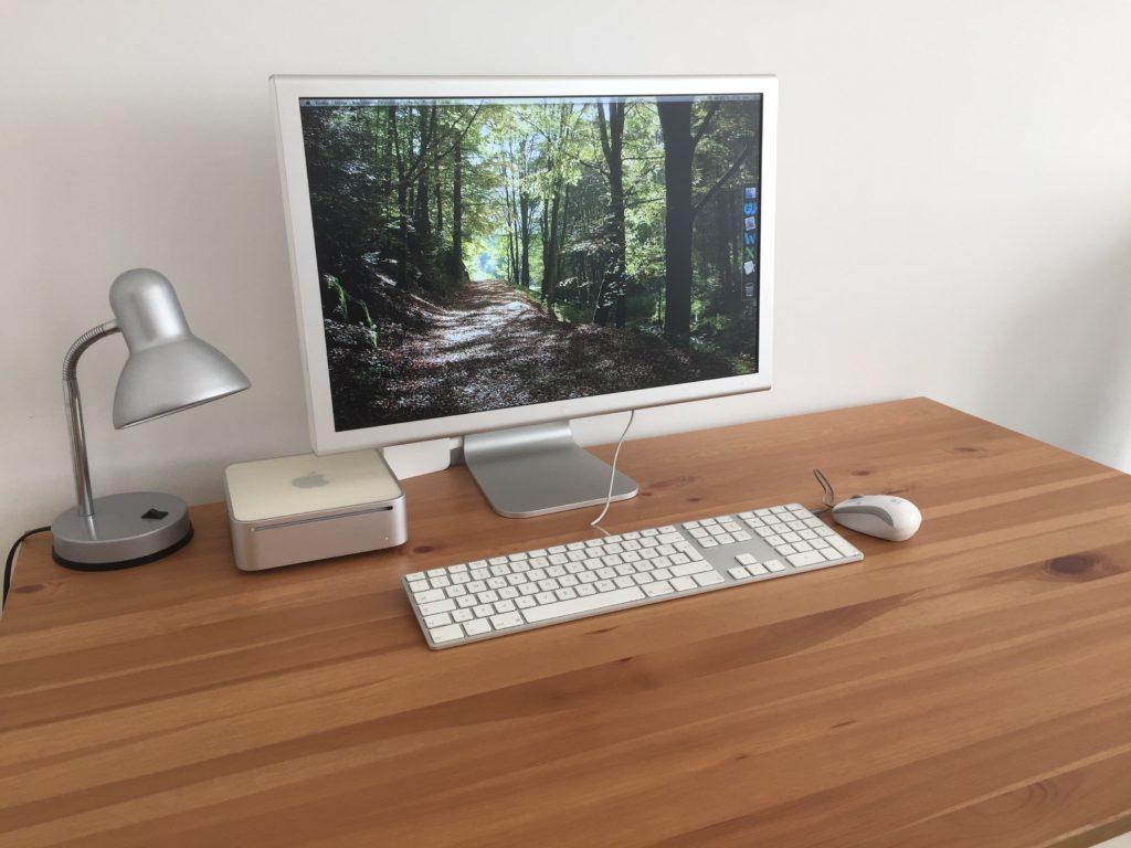 Kleiner quadratischer Computer mit Monitor, Tastatur und Maus auf einem Holztisch