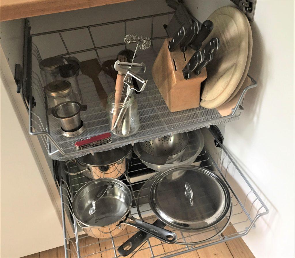 Blick in den Küchenschrank. Unten Töpfe, oben Messerblock, Holzbrettchen und einige Küchenutensilien