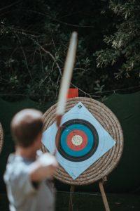Man zielt mit Bogen auf eine Zielscheibe