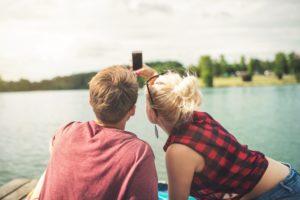 Mann und Frau am See sitzend, das Handy hoch haltend und hinein schauend
