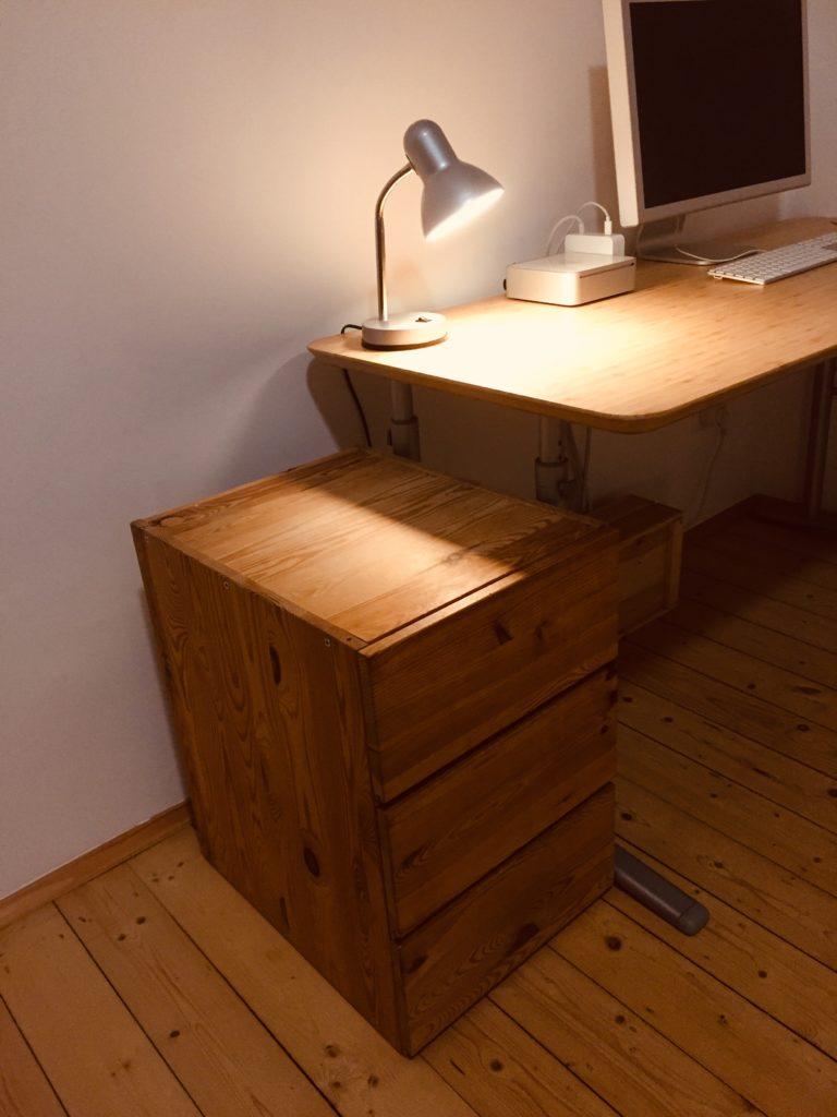 Holzkommode mit 3 Schubladen. Rechts davon eine kleine Lampe auf einem Schreibtisch
