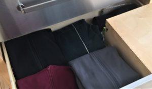Schublade mit Jacken und rechts einer Holzkiste