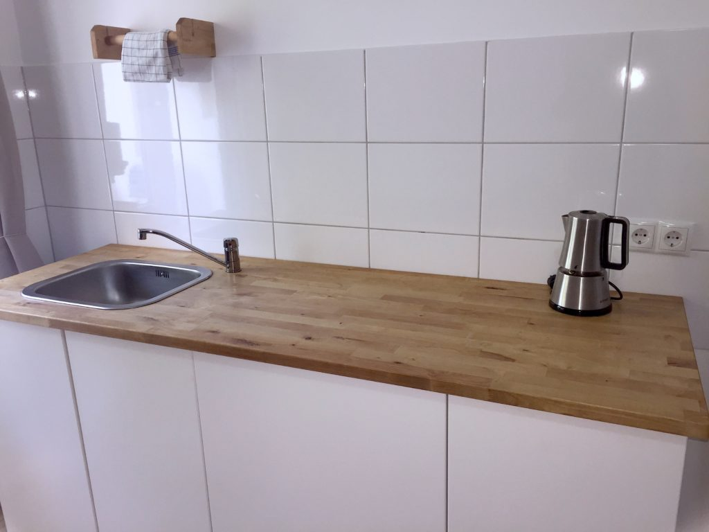minimalistische Küchenzeile mit Spülbecken links und Espressokocher rechts