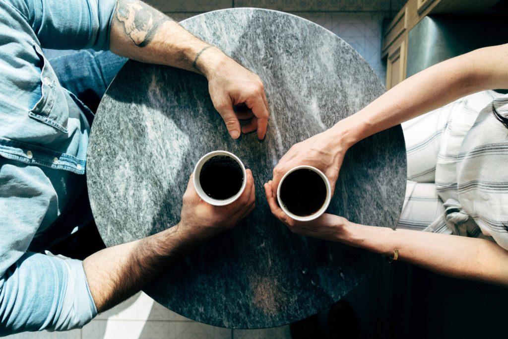 runter Tisch, Arme von Mann und Frau gegenübersitzend, eine Kaffeetasse umfassend