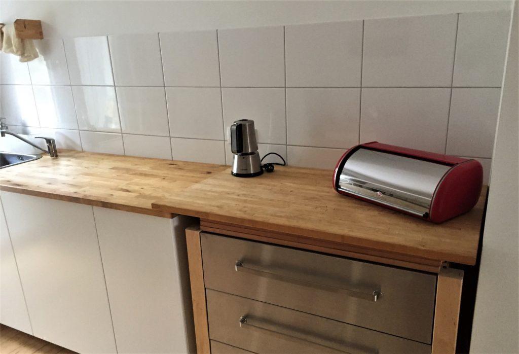 Küchenzeile links, rechts daneben ein Schubladenschrank mit lose aufliegender Arbeitsplatte