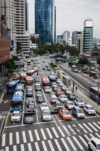 Viele Autos auf 6-spuriger Straße warten an einem Fußgängerüberweg