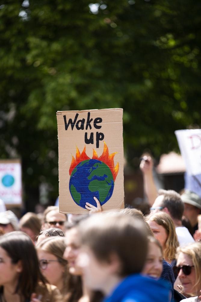 """Person hält Schild mit brennendem Planten und Aufschrift """"Wake up"""" in die Höhe"""