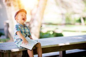 Kleiner Junge mit einem Buch sitzt lachend auf einer Bank