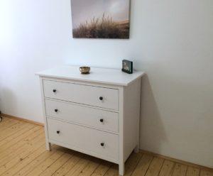 weiße Holzkommode mit 3 Schubladen und schwarzen Schubladenknöpfen