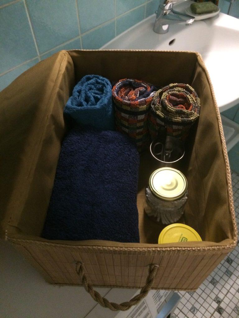 Blick in die Bambuskiste: Gerollte Handtücher, 2 Gläser, ein Edelstahlbehälter sind erkennbar.