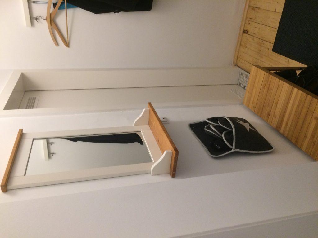 """Spiegel in einem kleinen Flur. Spiegel mit weißem Rand und Holzablage. Darunter ansatzweise Schuhbank aus Bambus und eine """"Pantoffel-Station"""""""