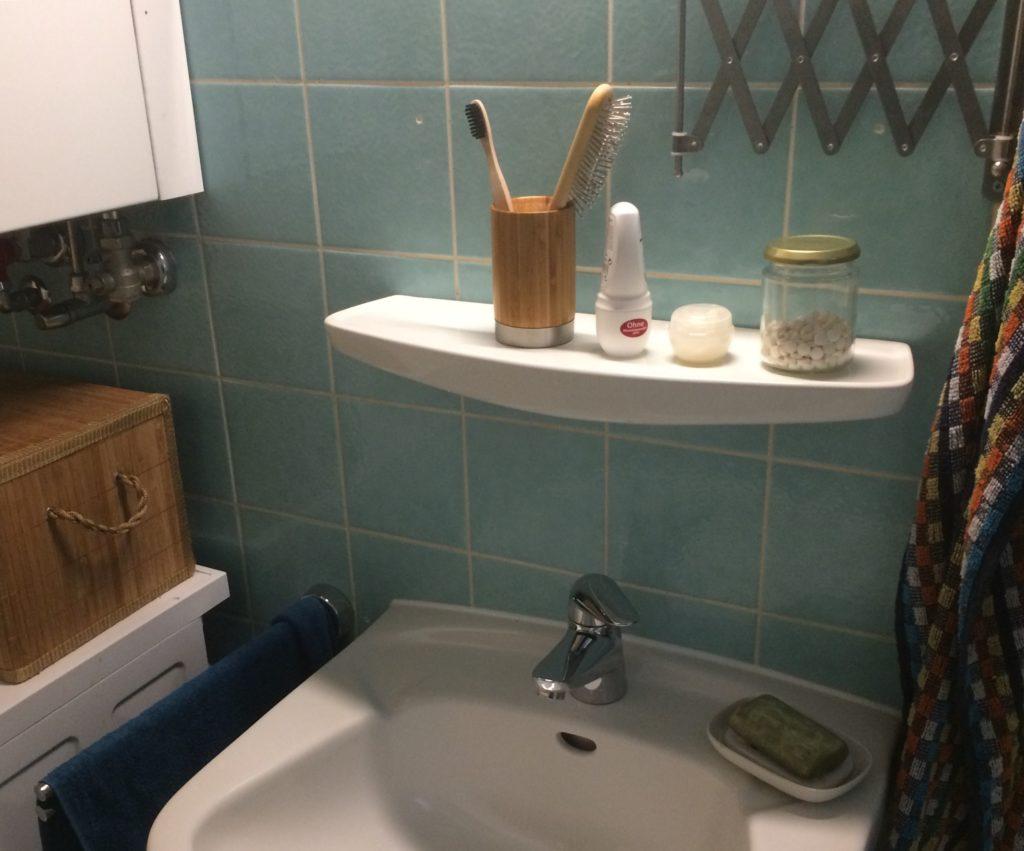 Waschbecken mit darüber befindlicher Ablage. Darauf Bambusbecher mit Zahnbürste, Haarbürste. Daneben Deo, Cremedöschen und ein Glas mit Zahnputztabs.
