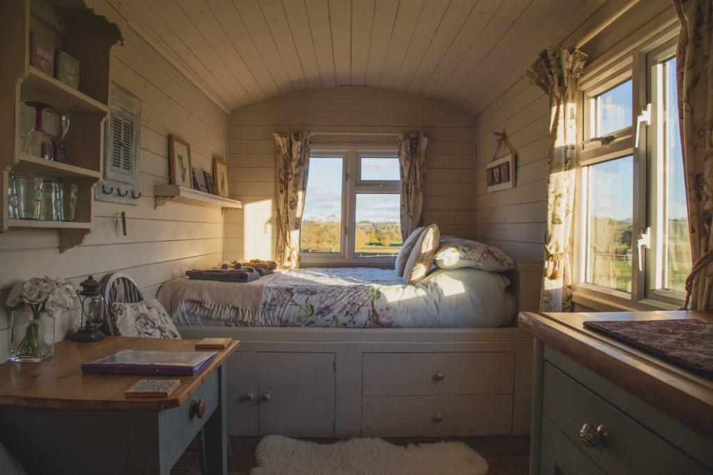 Blick in ein Tinyhouse. Geradeaus und rechts je ein Fenster. Geradeaus steht quer ein Bett über die ganze Breite. Rechts und Links ansatzweise Schränke erkennbar. Einige Regale an der Wand.