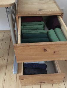 Schreibtischcontainer mit 2 geöffneten Schubladen. Obere Schublade: gefaltete Langarmshirts, untere Schublade: gefaltete Hosen