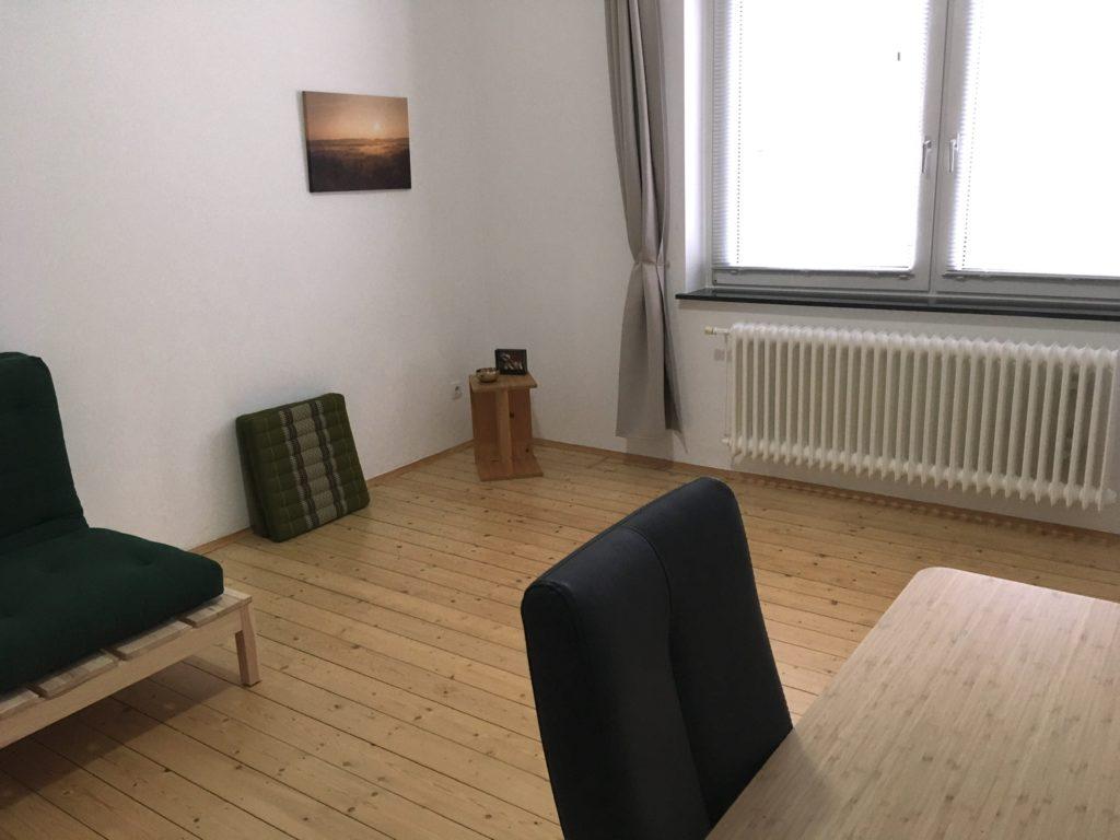Blick in Wohn-Schlafraum mit Futon, Kapokkissen, Hocker mit Klangschale und Bild, im rechten Vordergrund ansatzweise ein Schreibtisch mit Stuhl
