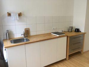 Küchenzeile mit Spüle links, einer Kochplatte und einem Schubladenschrank auf dem ein Espresskocher steht