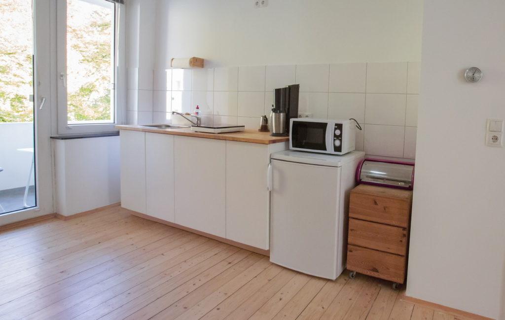 Blick auf Küchenzeile mit weißen Unterschränken und Holzarbeitsplatte. Rechts davon Kühlschrank mit darauf befindlicher Mikrowelle und ein kleiner Holzschrank