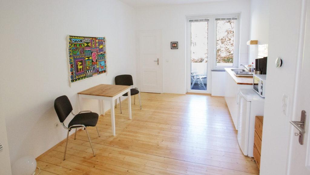 Blick in die Küche: Links Essplatz mit 2 Stühlen, geradeaus Balkontür und Fenster, rechts die Küchenzeile