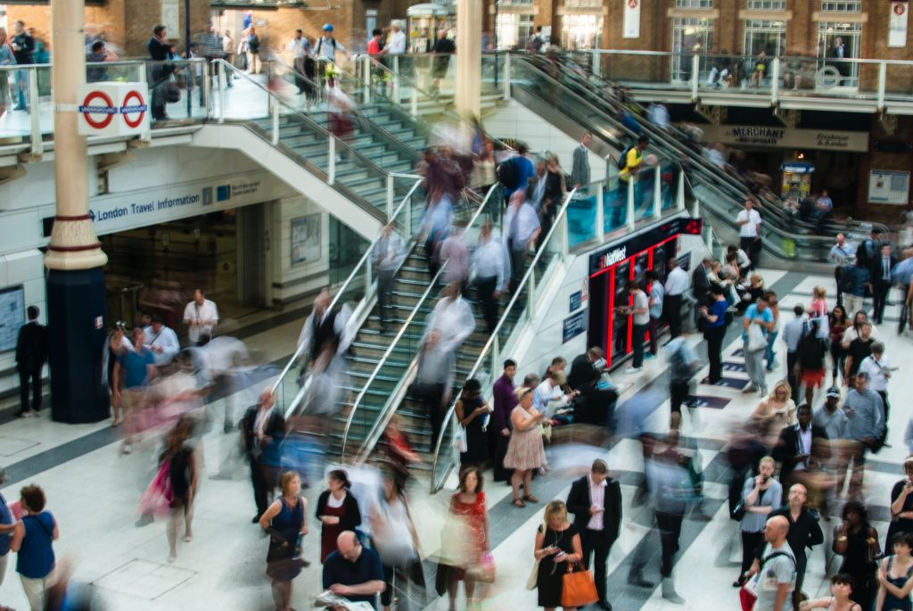 Blick auf Shoppingcenter mit Rolltreppe und vielen umherlaufenden Menschen