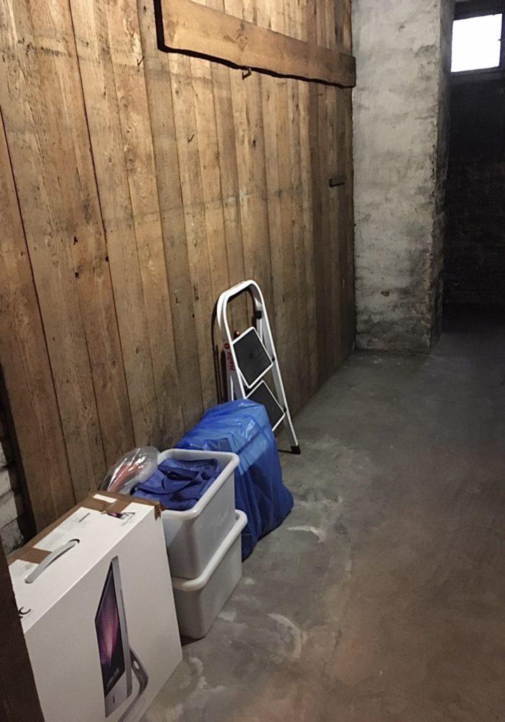 Kleiner Keller mit links an der Wand stehendem Karton, 2 Plastikkisten, ein blauer Müllsack und eine kleine Trittleiter