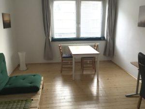 Blick in den Wohnraum mit Podesten und Futon links, geradeaus vor dem Fenster ein Tisch mit 2 Stühlen, rechts ansatzweise Stuhl und Schreibtisch erkennbar