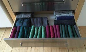Geöffnete Schublade mit Shirts, Hosen und Jacken