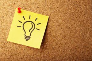 Pinwand aus Kork mit gelbem Zettel auf dem eine Glühbirne aufgemalt ist