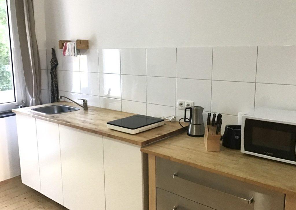Weißer Küchenblock mit Holzarbeitsplatte. Links Spüle, rechts eine mobile Kochplatte. Auf einem Schubladenschrank Espressokcoher, Messerblock, MIkrowelle