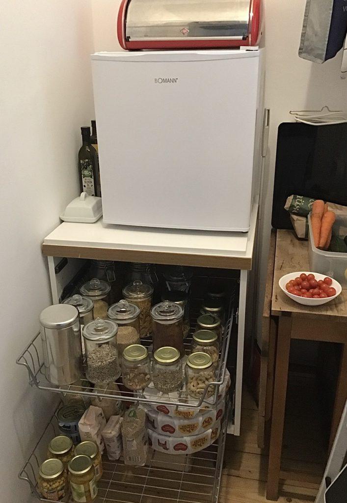 Abstellkammer mit Unterschrank. Im Unterschrank sind Lebensmittelvorräte zu sehen. Auf dem Unterschrank ein kleiner Kühlschrank, darauf eine Brottrommel. Rechts ein schmaler Klapptisch mit eingem Gemüse darauf.