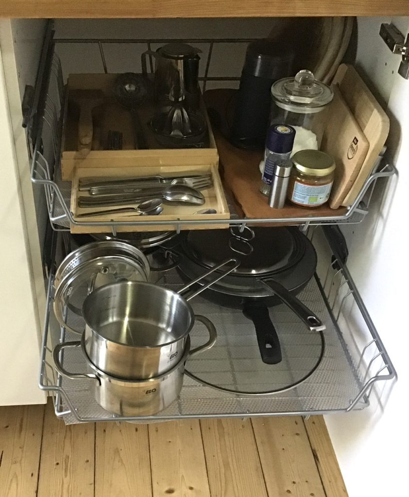 Küchenschrank mit 2 ausziehbaren Drahtkörben. Oben Besteck, Gewürze, einige Küchenhelfer. Unten Töpfe und Pfannen.