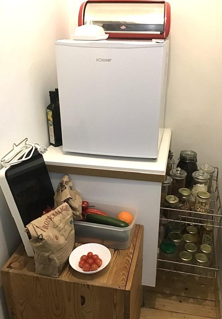 Abstellkammer mit Unterschrank, Kühlschrank. Vorne kleiner Schubladenschrank auf dem sich einiges Obst- und Gemüse befindet