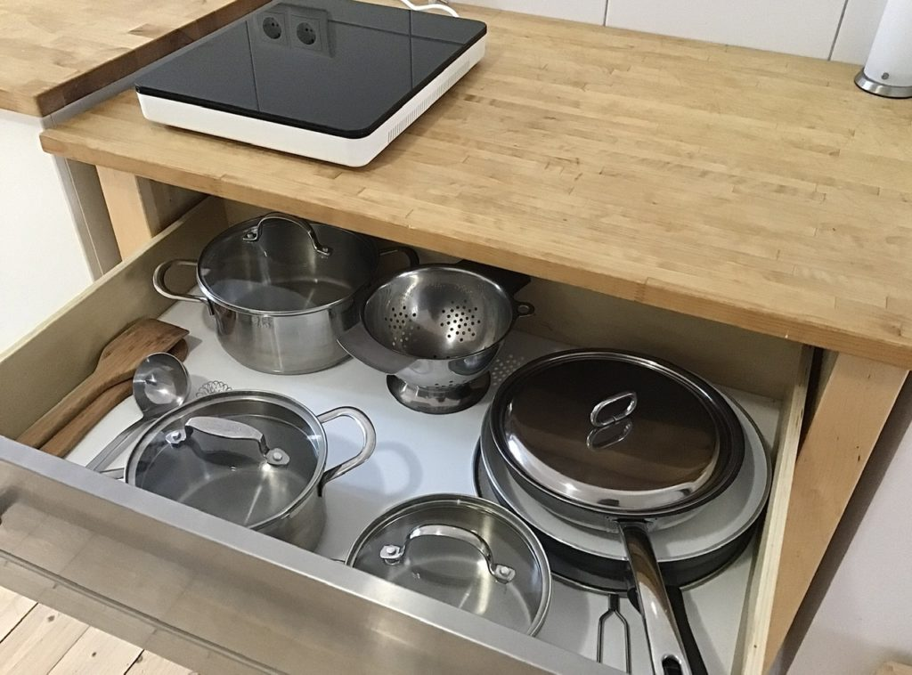 Induktionskochplatte auf Holzarbeitsplatte. Darunter eine geöffnete Schublade mit Pfannen, Töpfen, Pfannenwender, Kochlöffel