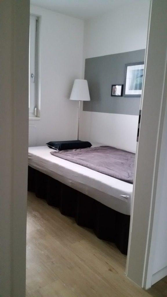 Blick durch eine geöffnete Tür ins Schlafzimmer auf ein Bett, Stehlampe. An der Wand 2 Bilder