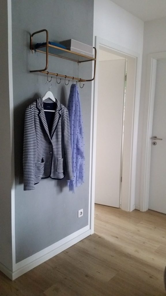 Flur mit Flurgarderobe. an der Garderobe ein Blazer, sowie Schal. Die Garderobe hat oben eine Ablage. Darauf ein grauer Kasten, sowie vermutlich ein Schal