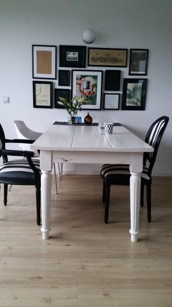 Älterer, weiß lackierter Esstisch mit 3 Stühlen. An der Wand 11 Bilder zum Rechteck angeordnet