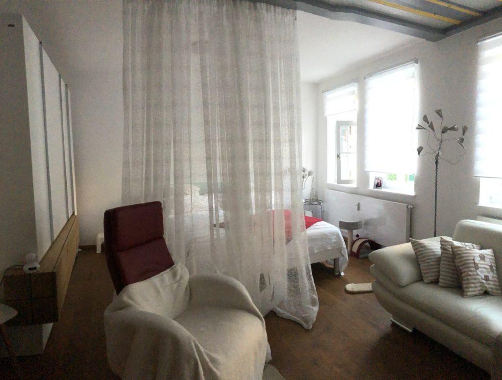 Wohnraum mit Sessel und Sofa im Vordergrund. Im hinteren Bereich durch eine Gardine getrennt der Schlafbereich mit Doppelbett