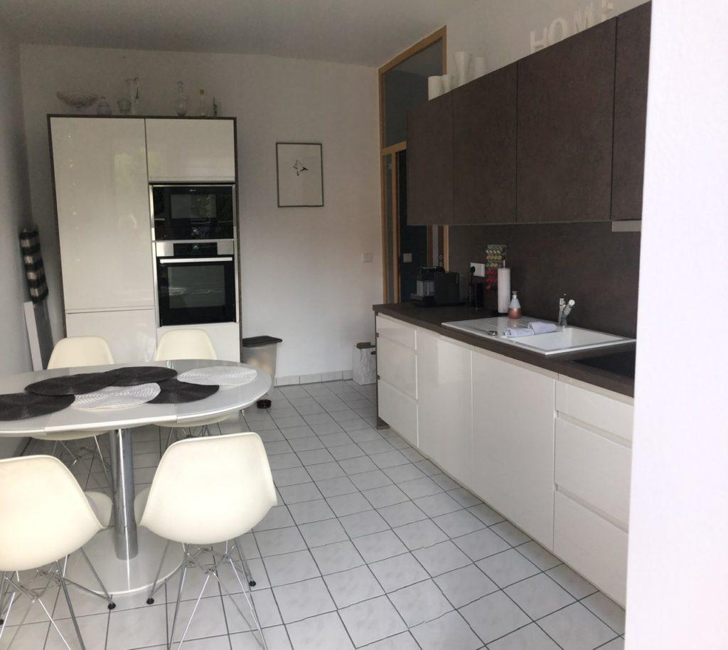 Küche in weiß mit braunen Akzenten - mit Esstisch und 4 Stühlen links. Geradeaus Doppelschrank mit Kochzone. Rechts Küchenzeile mit Spüle