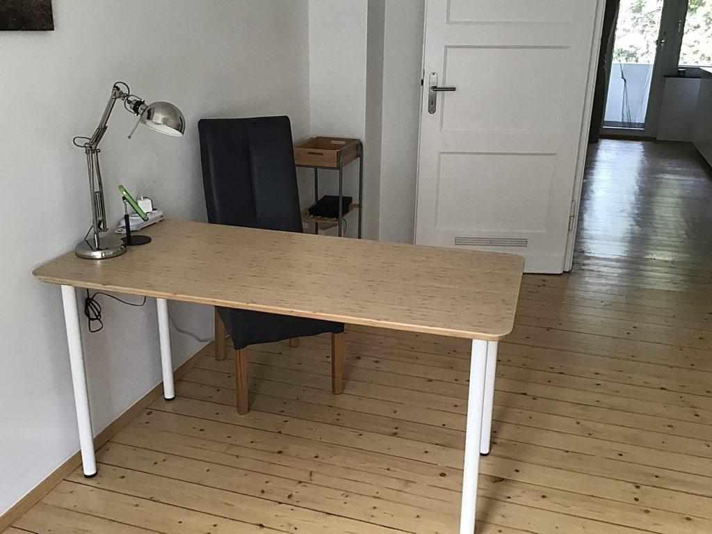 Schreibtisch mit Bambusplatte und weißen Beinen. Darauf eine Lampe. Vor dem Schreibtisch ein Stuhl. Im Hintergrund ein kleines Regal