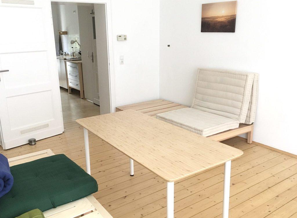 Zwei Podeste mit 1x1m Größe und Kapokklappmatratze. Im Vordegrund Tisch und ansatzweise das Multifunktionsmöbel