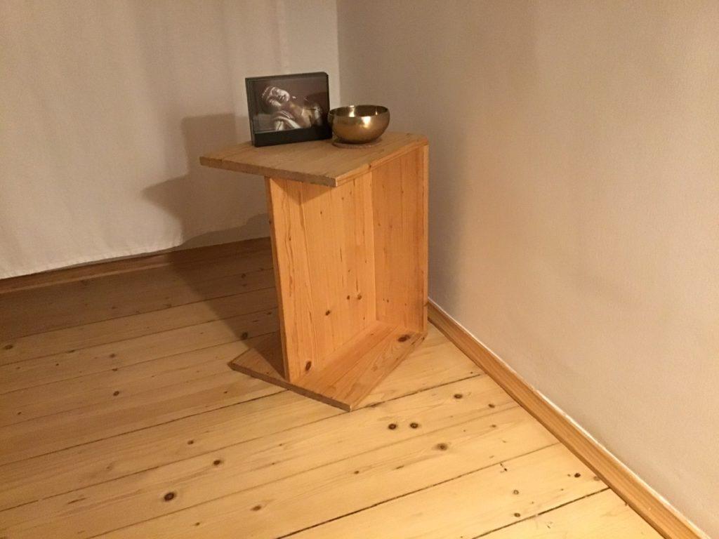 Berliner Hocker mit Klangschale und einem Bild einer Meditationsfigur