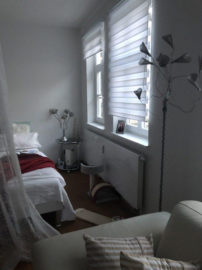 Zwischen Bett links und Fenster rechts ein Katzenbaum vor der Heizung