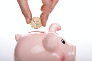 Jemand wirft eine kleine Münze in ein rosa Sparschwein