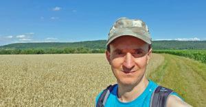 Portrait Christof Hermann beim Wandern bei blauem Himmel und Feld im Hintergrund