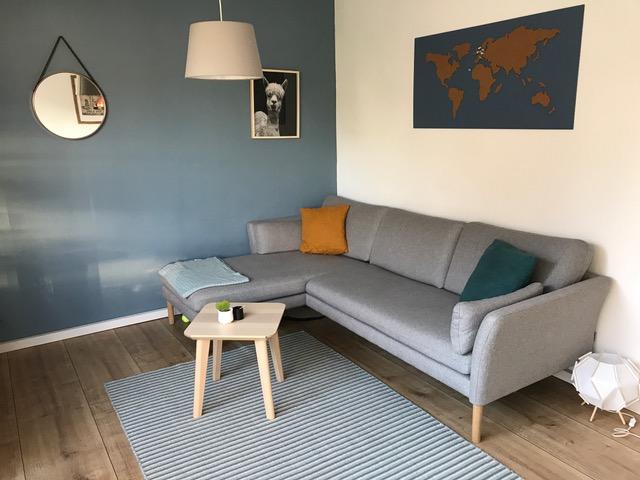 graues, schlichtes Sofa mit Holzbeinen in einerZimmerecke, davor ein heller Holzhocker als Sofatisch