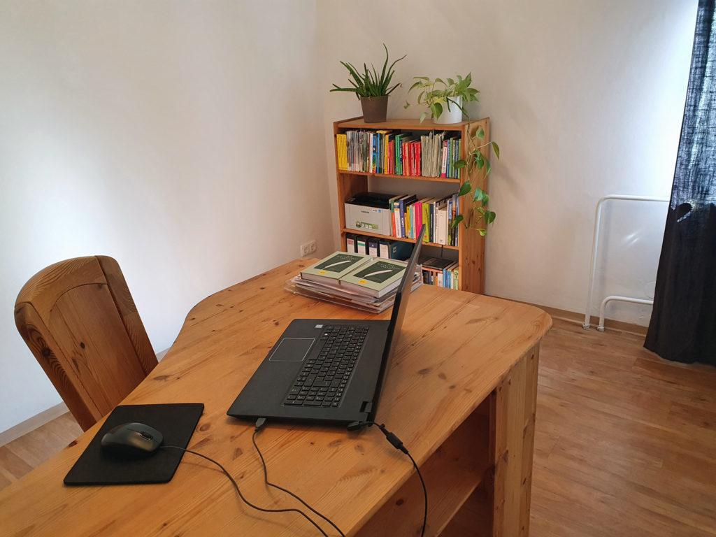 Arbeitszimmer: Blick auf Schreibtisch mit Laptop, Maus, einigen Unterlagen. Im Hintergrund ein Bücherregal