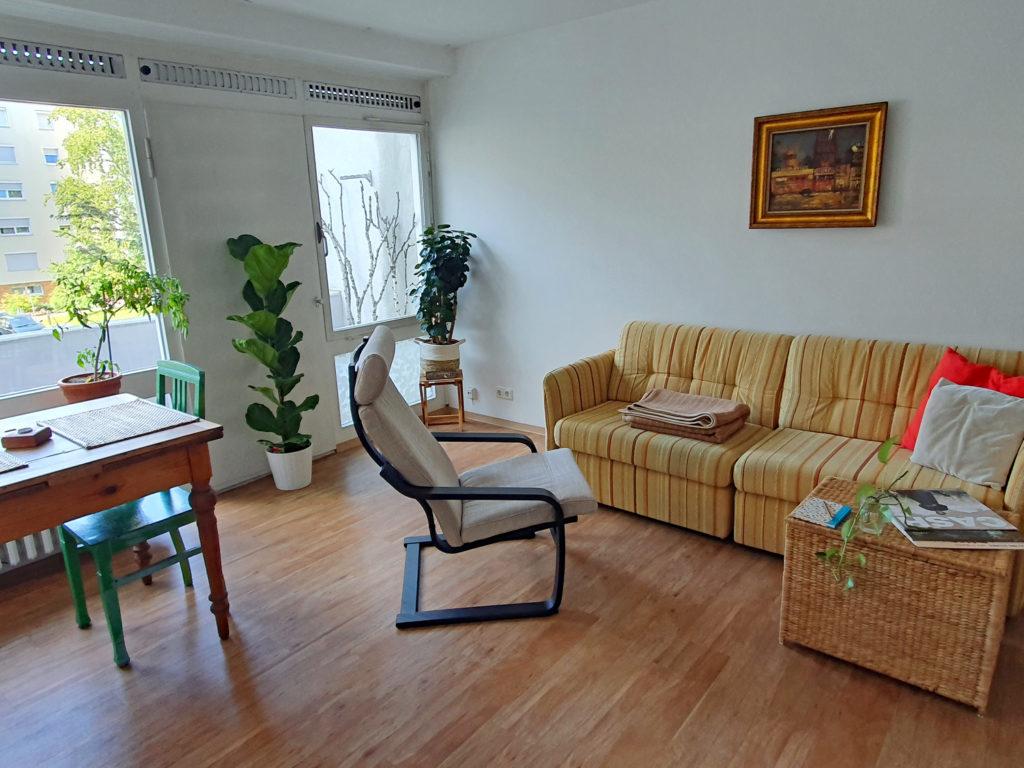 Wohnzimmer: links am Bildrand Esstisch, rechts Sofa, davor ein Sessel und eine Korbtruhe, die als Tisch genutzt wird
