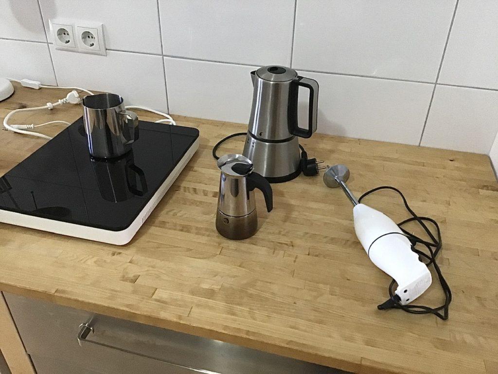 Links eine Kochplatte mit Milchkännchen. In der Mitte ein großer und ein kleiner Expressokocher. Rechts ein Stabmixer
