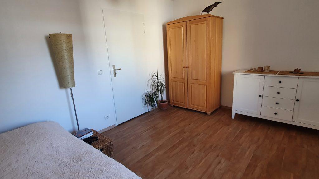 Schlafzimmer - links unten am Bildrand Bett, rechts Kleiderschrank und Kommode