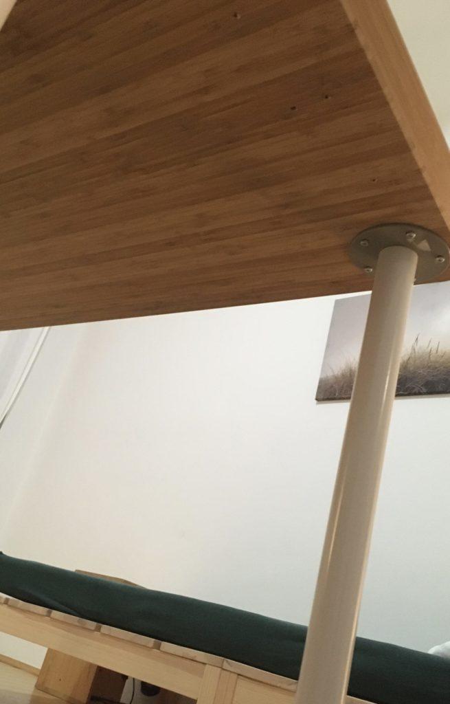 Teil eines Tischs von unten fotografiert. Im Hintergrund Teil eines Bettpodestes