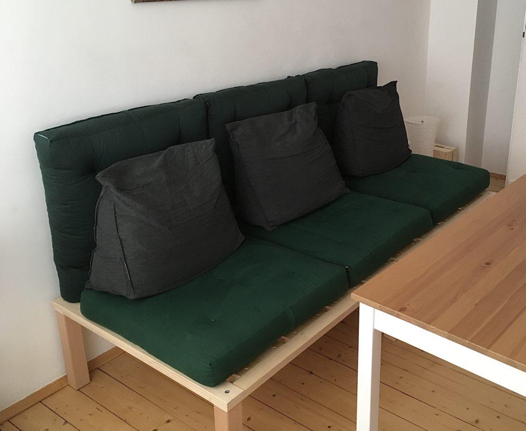 Holzgestell für ein Bett ohne Kopf und Fußteil mit 2 Klappfutons und 3 Kissen als Sitzpolster